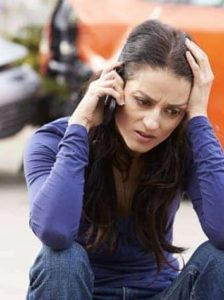 Woman making a call after a car accident