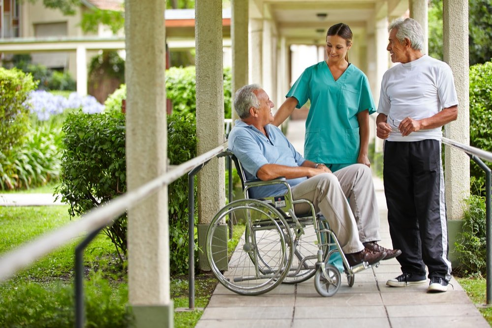 Elders and a nurse talking outside in the nursing home.