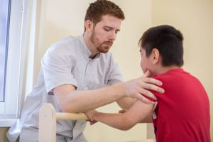 Physical therapist helping cerebral palsy patient.