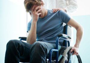 Depressed man in wheelchair suffering from paraplegia.