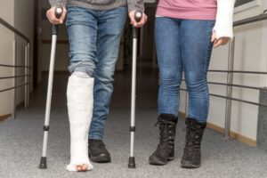 Two persons with cast on on leg and arm.