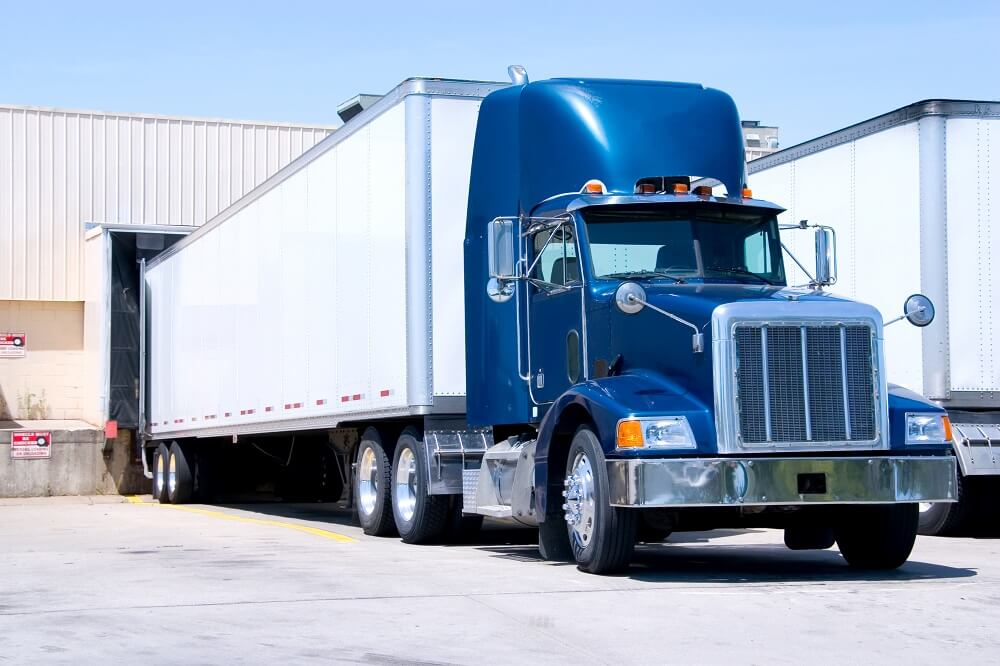 Blue tractor trailer truck in parking.